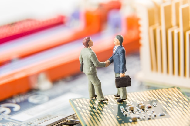 Two miniature businessmen it managers shaking hands while standing on cpu and computer motherboard.