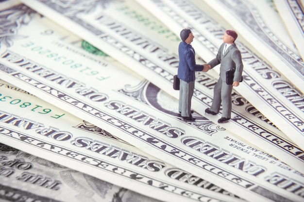 Two miniature businessmen shaking hands while standing on american dollar money.