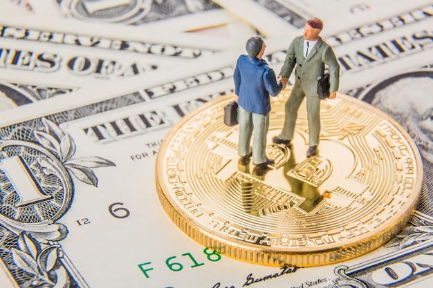 Two miniature businessmen shaking hands while standing on bitcoin cryptocurrency and american dollar money.
