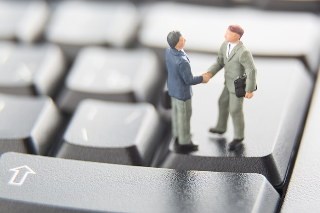 Two miniature businessmen shaking hands while standing on the keys of a black keyboard.