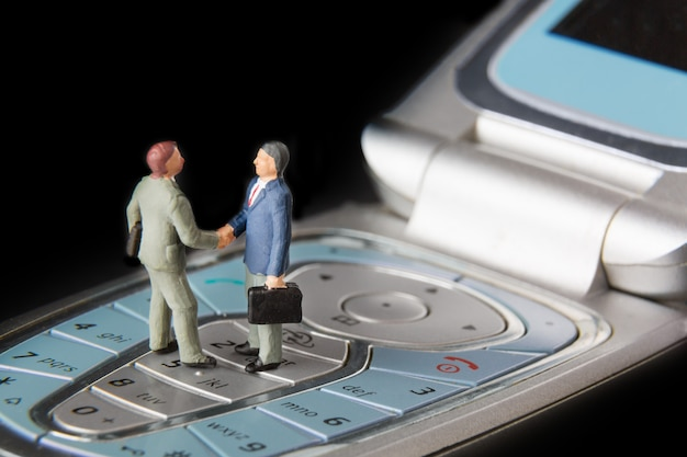 Two miniature businessmen shaking hands while standing on the keys of a mobile phone