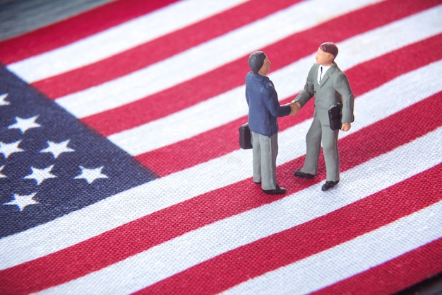 Two miniature businessmen shaking hands while standing on usa american flag.