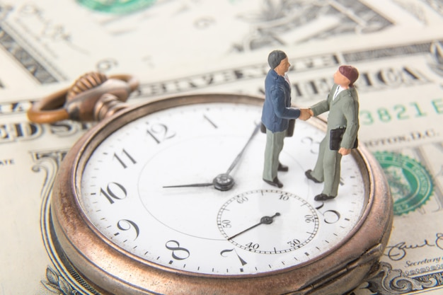 Two miniature businessmen shaking hands while standing on vintage old clock and american dollar money.