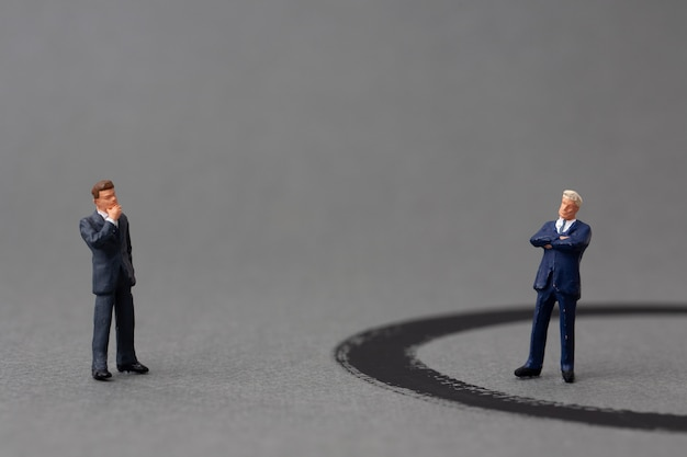 Two miniature businessmen stand on opposite sides