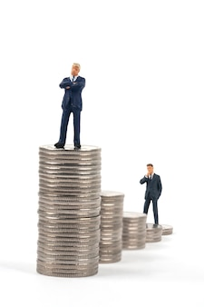 Two miniature businessmen standing on coin stacks