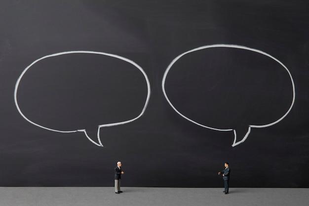 빈 말풍선이 있는 칠판 배경에 대해 이야기하는 두 명의 미니어처 사업가