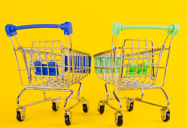 Two miniature green and blue shopping cart on yellow background