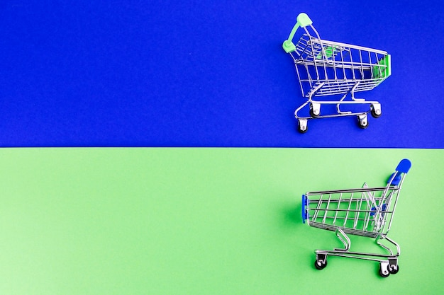 Two miniature shopping cart on blue and green dual background