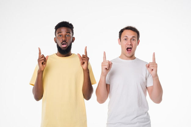 Two mixed race handsome men posing together pointed up isolated over white wall