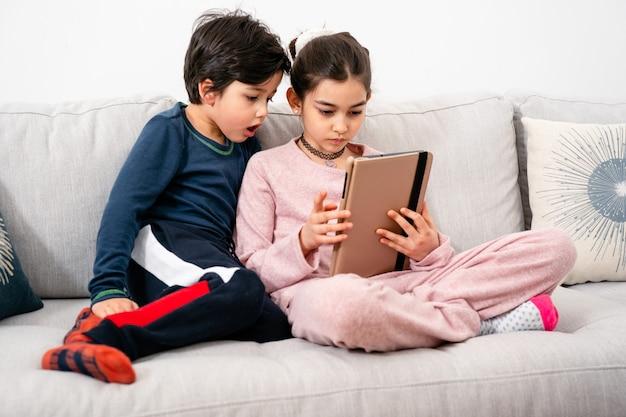 태블릿과 함께 소파에 앉아 두 혼혈 아이. 실생활, 다양성, 디지털 기술