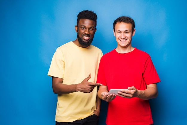 Two mixed race men looking at the phone isolated on blue wall