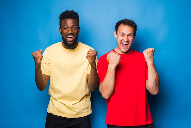 Two mixed race men with win gesture isolated on blue wall