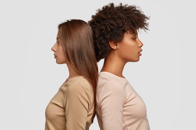Due donne di razza mista stanno di profilo l'una all'altra, hanno espressioni pensose, vestite con abiti casual