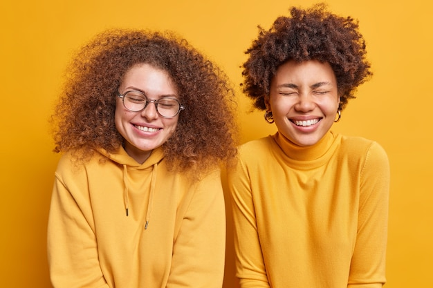 Two mixed race women with curly hair have happy expressions giggle positively stand next to each other close eyes from joy spend free time together isolated over yellow wall. emotions concept