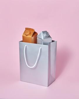 Два макета упаковки для молочных продуктов золотого и серебряного цвета в бумажном серебряном мешочке на пастельно-розовом фоне с мягкими тенями, копией пространства. экологичная концепция. концепция утилизации.