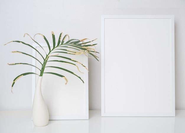 흰색 테이블과 벽 배경에 현대 흰색 꽃병에 말린 야자수 잎 두 흰색 나무 포스터 프레임 장식을 모의