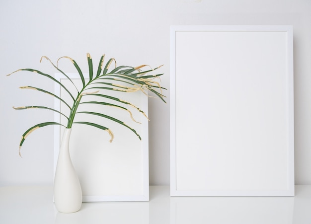 Two mock up white wooden poster frame decor with dried palm leaves  in modern white vase on white table and wall background