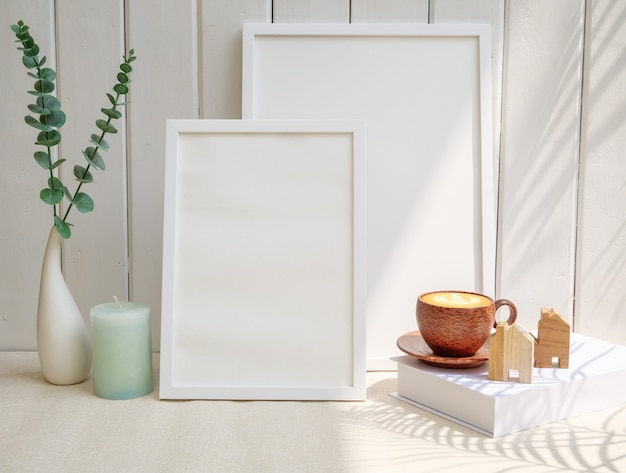 2つのモックアップ画像フレーム木製コーヒーカップキャンドルハウスモデルと木製のテーブルの上のモダンなセラミック花瓶のユーカリの葉白い背景白い部屋のインテリアの朝食長い影