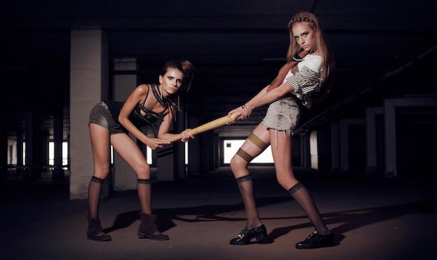 Две модели брюнетка и блондинка позируют на стоянке. брутальные девушки в стиле постапокалипсис
