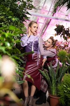 2 つのモデル。温室で一緒にポーズをとるポジティブな素敵な姉妹