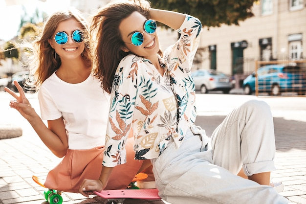 Two models in summer sunny day in hipster clothes sitting on penny skateboard on the street