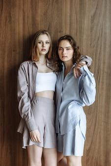 두 모델 여성은 새로운 여름 옷 컬렉션에서 셔츠와 반바지를 입고 스튜디오에 서서 나란히 포즈를 취합니다.