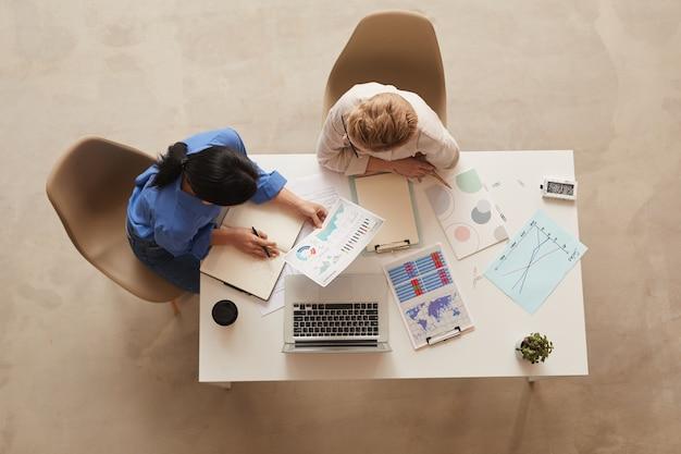 テーブル、コピースペースに座ってデータチャートについて話し合う2人の現代のビジネスウーマン