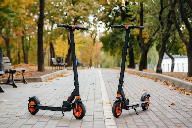 日没時に公園にある2台のモダンな電動スクーター。環境車両。環境への配慮。