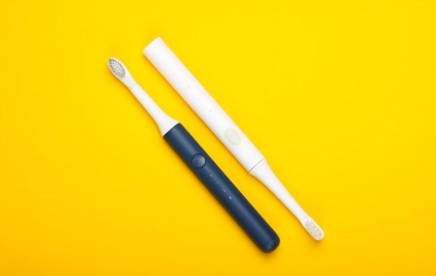 Две современные электрические зубные щетки на желтой поверхности