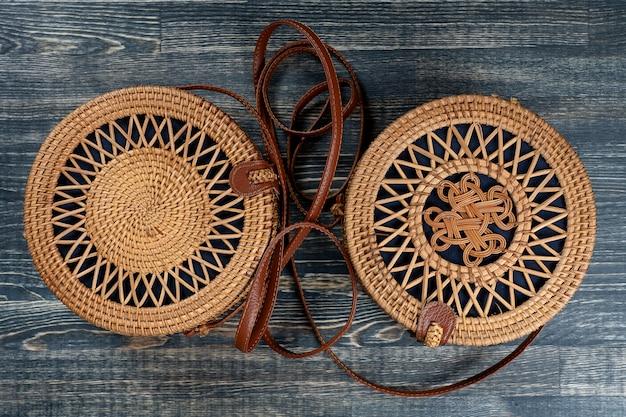 Две современные стильные круглые соломенные сумки на деревянном