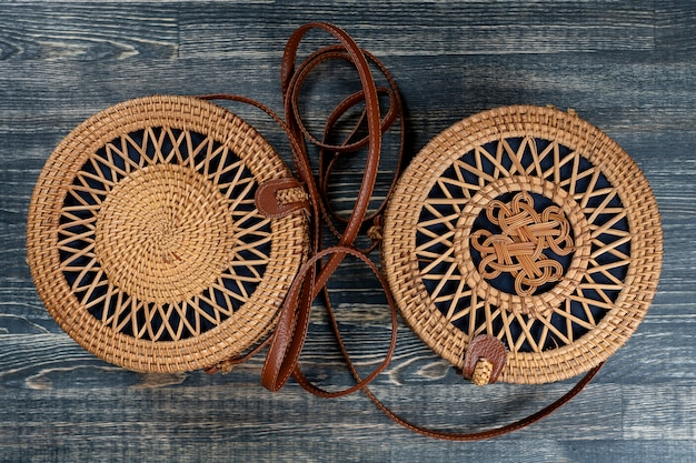 Two modern stylish round straw bag on the wooden