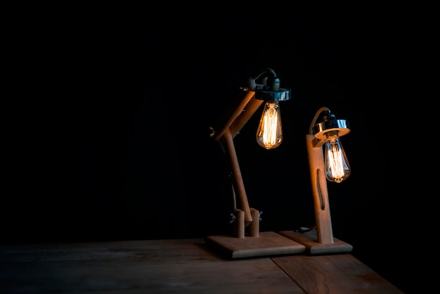 Two modern wooden designer table lamps on black. interior design. horizontal copy space. .