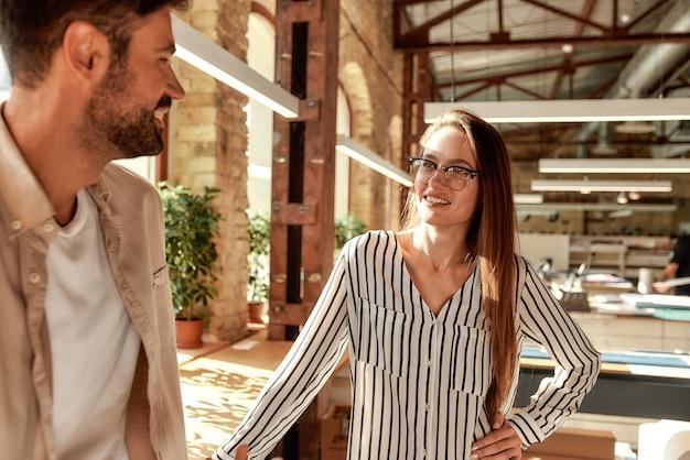 クリエイティブオフィスに立っている間に何かについて話している2人の現代の若者コーヒーブレイク