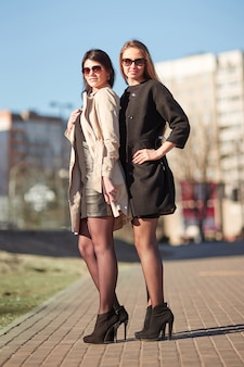 Two modern young women looking at a tall office building