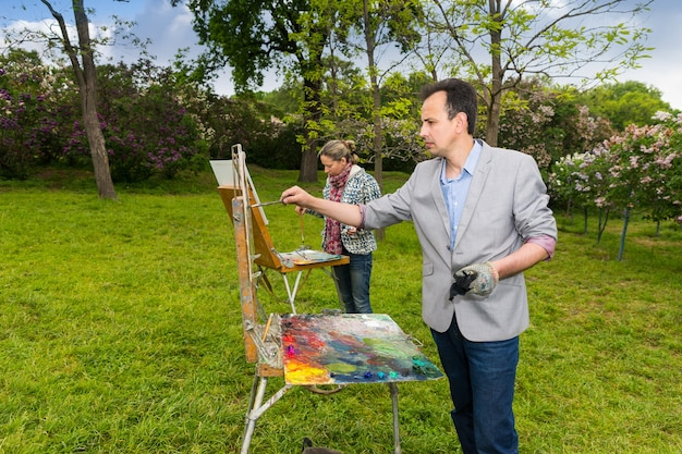 스케치북 앞에 서있는 두 명의 겸손한 화가가 공원에서 미술 수업을하는 동안 오일과 아크릴로 그림을 그립니다.