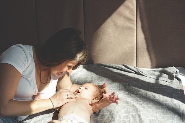 Двухмесячный малыш без одежды, голый, лежащий на кровати в подгузнике и улыбающийся маме