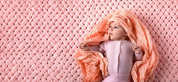 Двухмесячный малыш в розовом костюме на вязаном пледе, панорамный