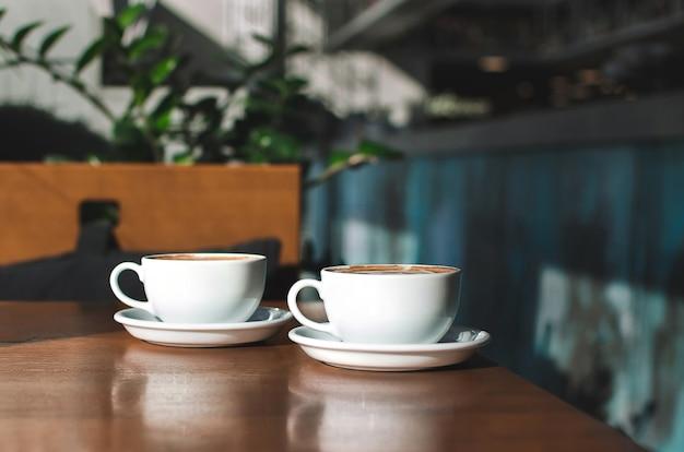 木の上のコーヒーの2つの朝のカップ