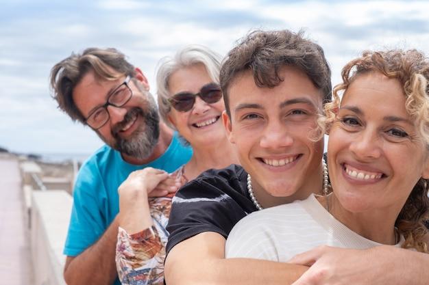 두 명의 어머니와 다른 연령대의 두 아들, 다세대 가족. 포옹 하 고 카메라를보고 웃 고