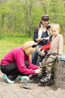 幼い息子に合わせて石垣に座る 2 人の母親