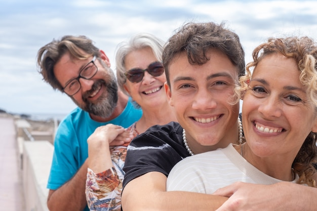 Two mothers and two son of different ages, multi-generation family. smiling hugging and looking at camera