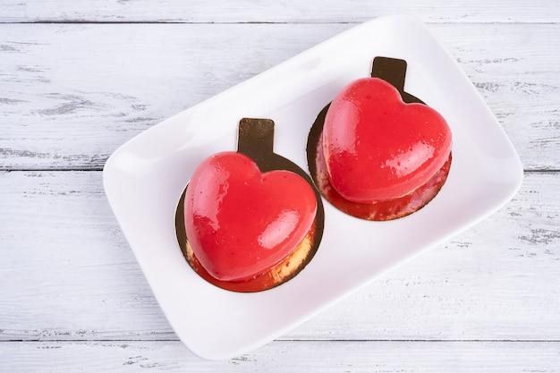 白い木製の背景の上の白いプレートに赤いハートの形で2つのムースケーキ