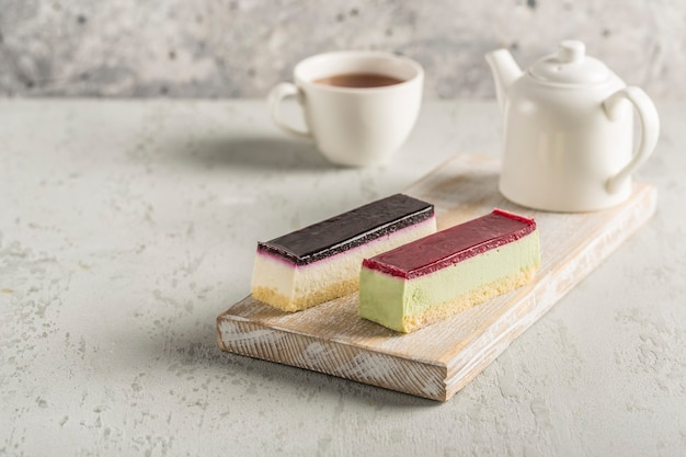 주전자와 차 한잔이있는 나무 보드에 다른 설탕을 입힌 두 개의 무스 케이크