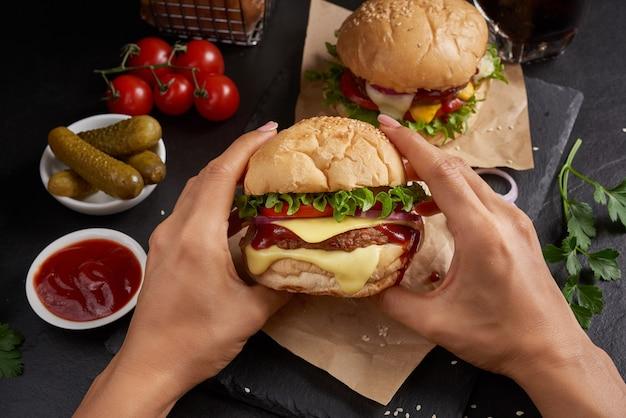 Два аппетитных, домашний гамбургер со свежими овощами и сырным салатом и майонезом подается, картофель фри. женская рука с вкусным гамбургером на черном каменном столе. концепция быстрого питания и нездоровой пищи