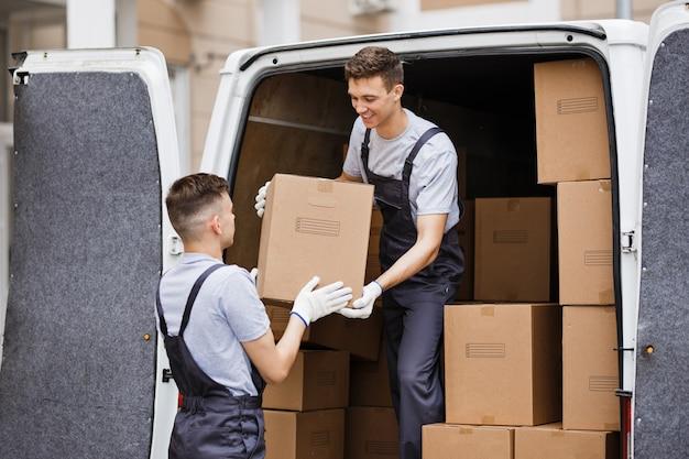 制服を着た2人の引っ越し業者が箱でいっぱいのバンを降ろしていますハウスムーバー引っ越し業者サービス