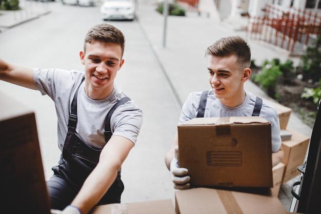 制服を着た2人の引っ越し業者が箱でいっぱいのバンを降ろしています