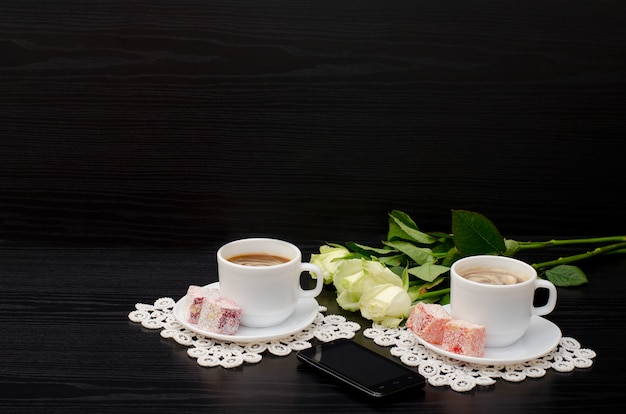Two mugs of coffee with milk, turkish delight on a saucer, white roses on a black. copyspace