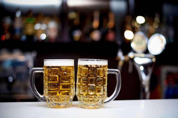 Two mugs of cold beer stand on the bar.