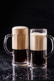 Two mugs of frothy beer