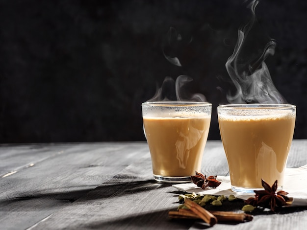 Two mugs of masala tea are on a gray table. steam comes from them. hard light, dark background.